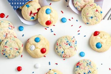 overhead shot of patriotic cookies in red white and blue bags surrounded by festive sprinkles for recipe card