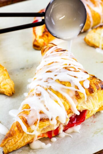 black spoon drizzling icing on a baked turnover on a baking sheet