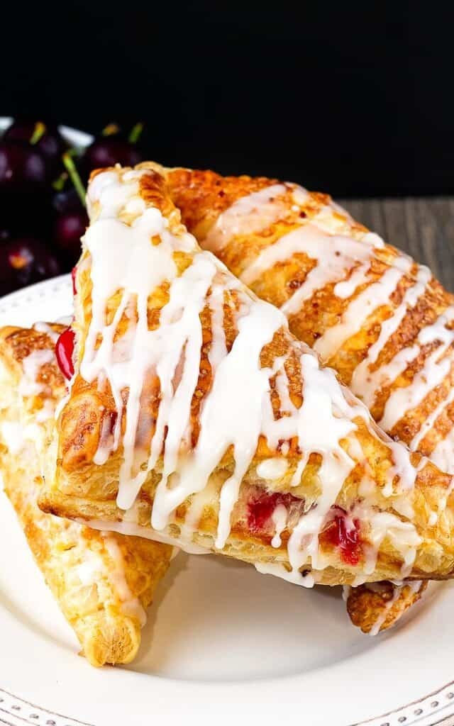 three cherry turnovers, drizzled with icing, on a white cake plate