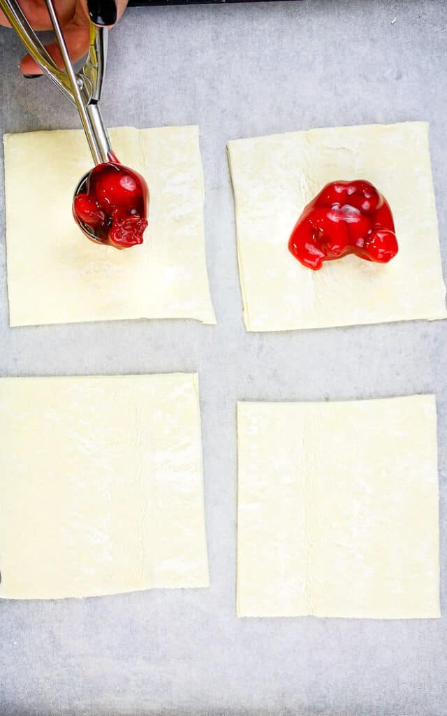 four squares of puff pastry on a baking sheet two have pie filling