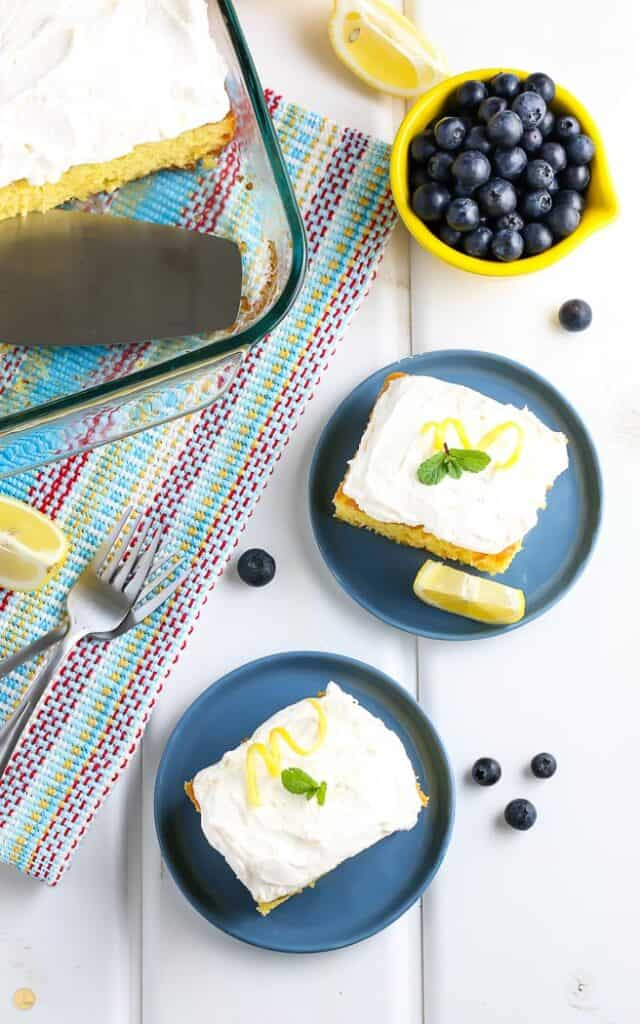 yellow cake with two pieces cut and placed on small blue plates with bowl of blueberries next to it