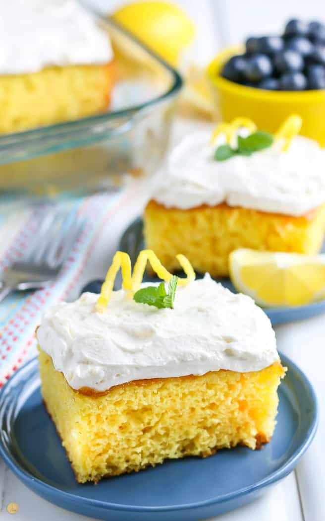 square of lemonade cake on a blue plate with mint garnish. other cake slices in the background.