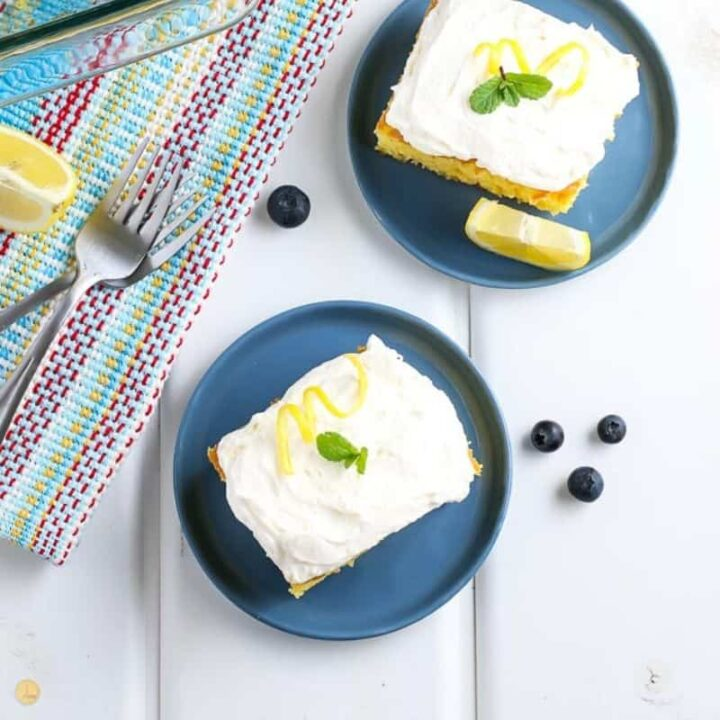 two pieces of lemonade cake on two small blue plates with two forks and a few scattered blueberries