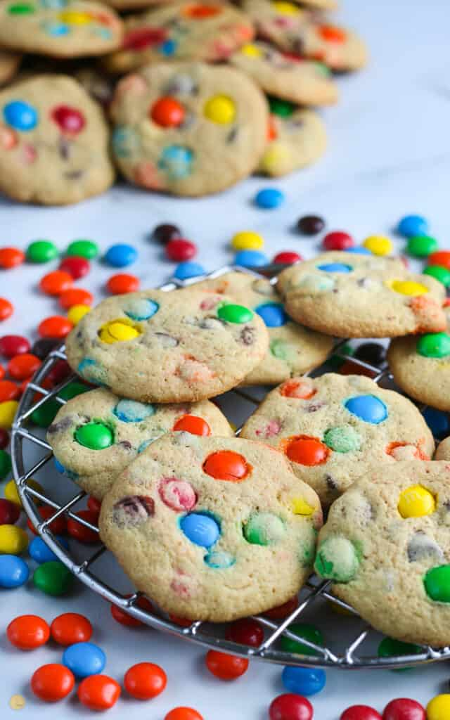 side pick of M&M cookies on a wire cooling rack with candy spread around it