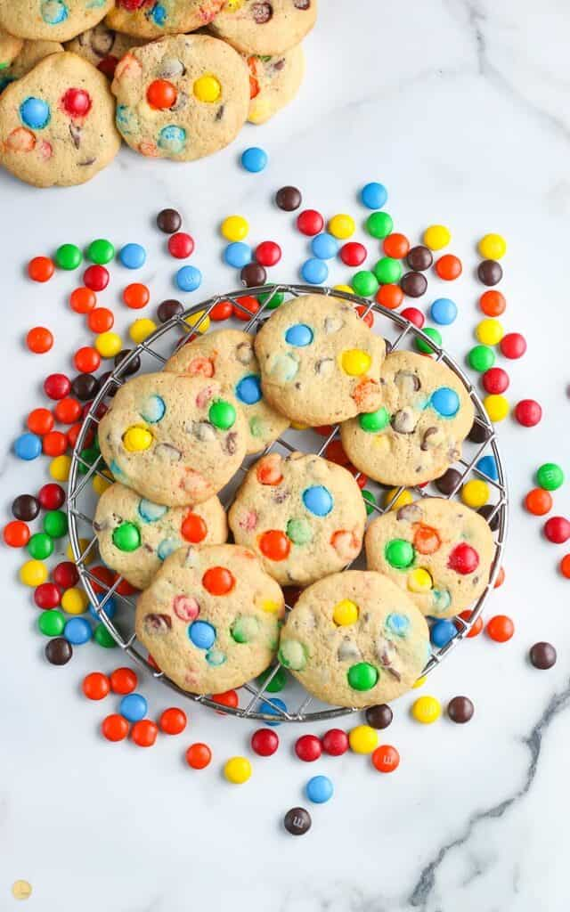 overhead pic of M&M cookies on a wire cooling rack with candy spread around it