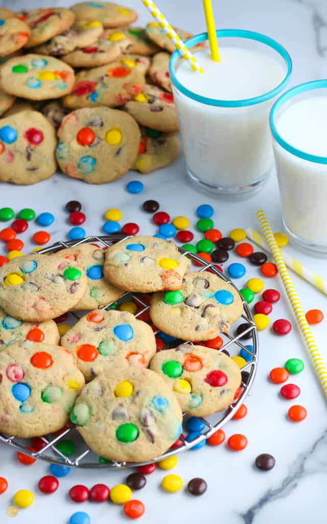 M&M Cookies on a wire rack next two two glasses of milk with yellow straws