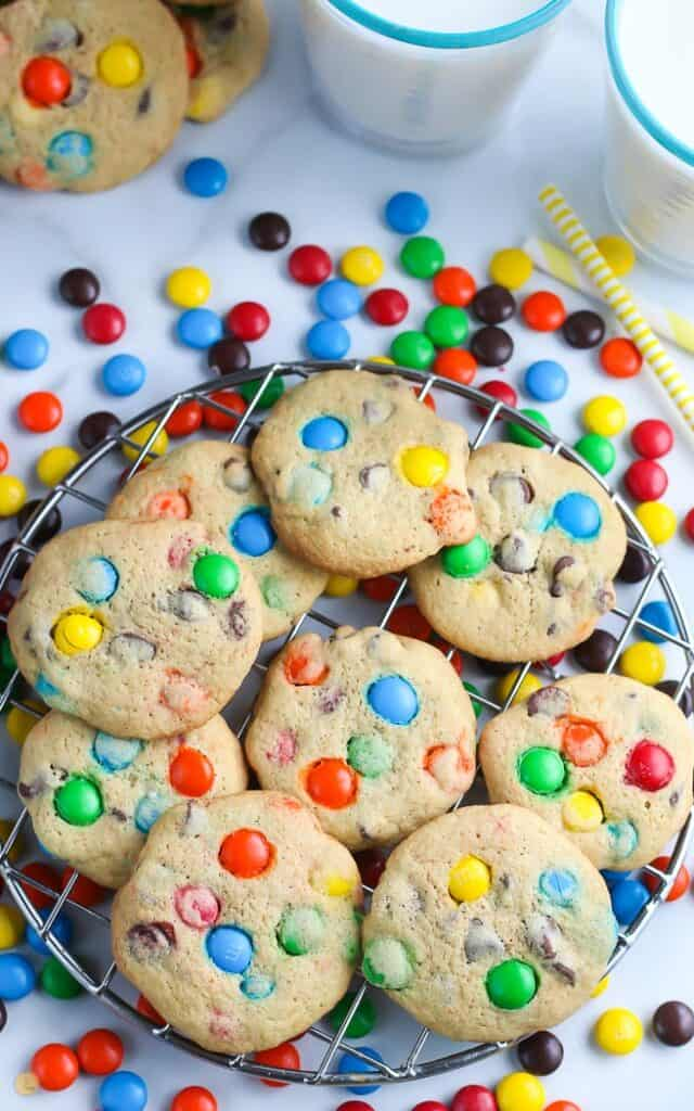 overhead picture of cookies with M and M candy on cooling rack with two glasses of milk and yellow straw