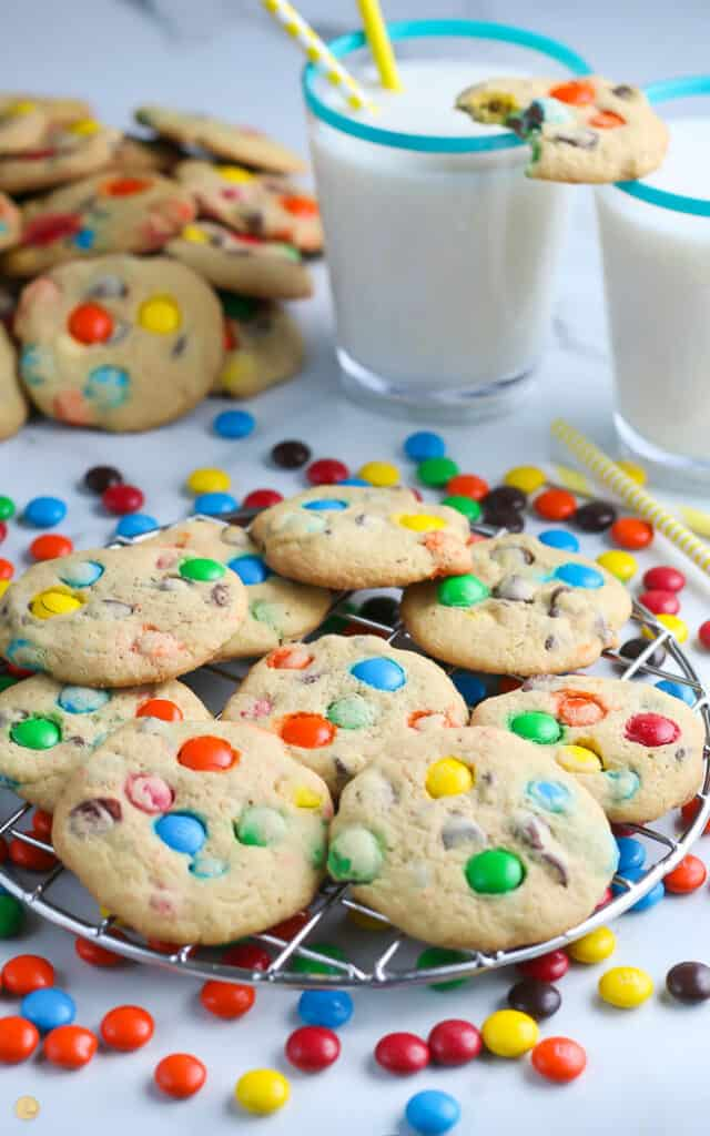 side view of M&M cookies on a cooling rack with glasses of milk in the background with a cookie balanced on them