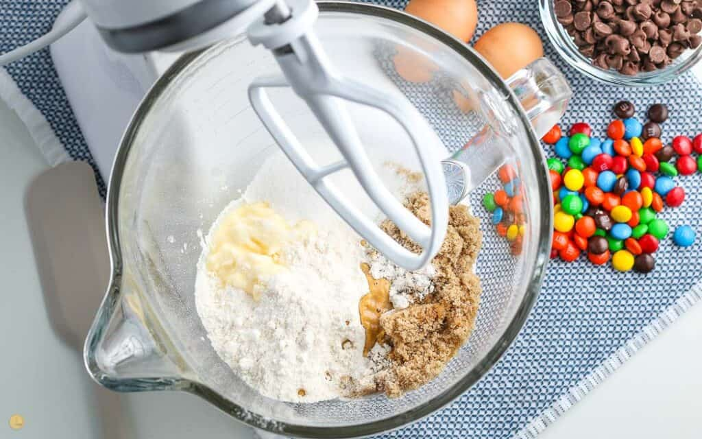 over head picture of stand mixer with cookie dough ingredients in the bowl on a blue placemat with a bowl of M&Ms next to it