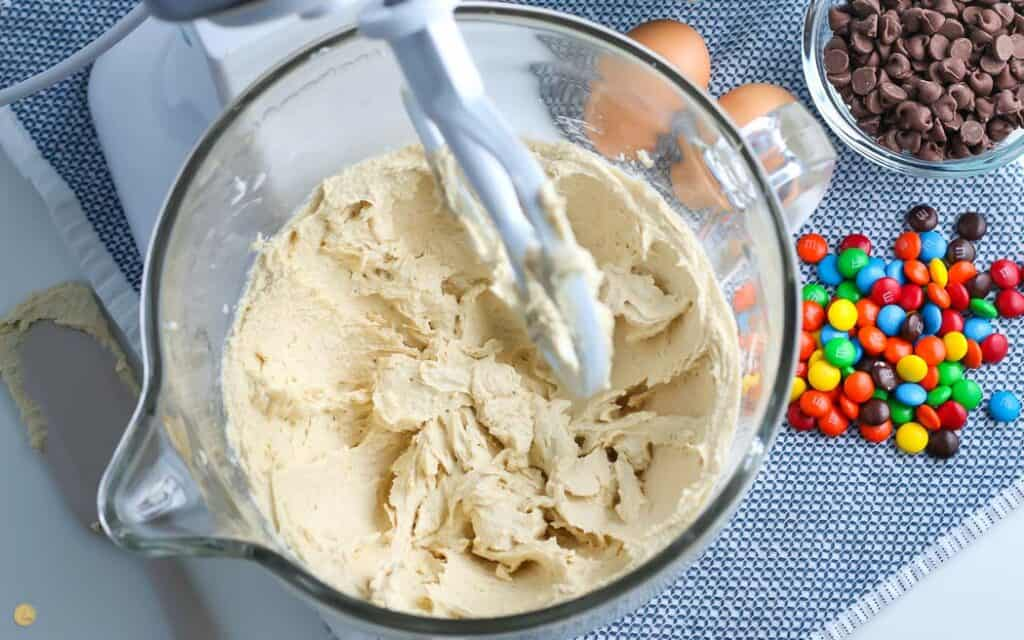over head picture of stand mixer with mixed cookie dough ingredients in the bowl on a blue placemat with a bowl of M&Ms next to it