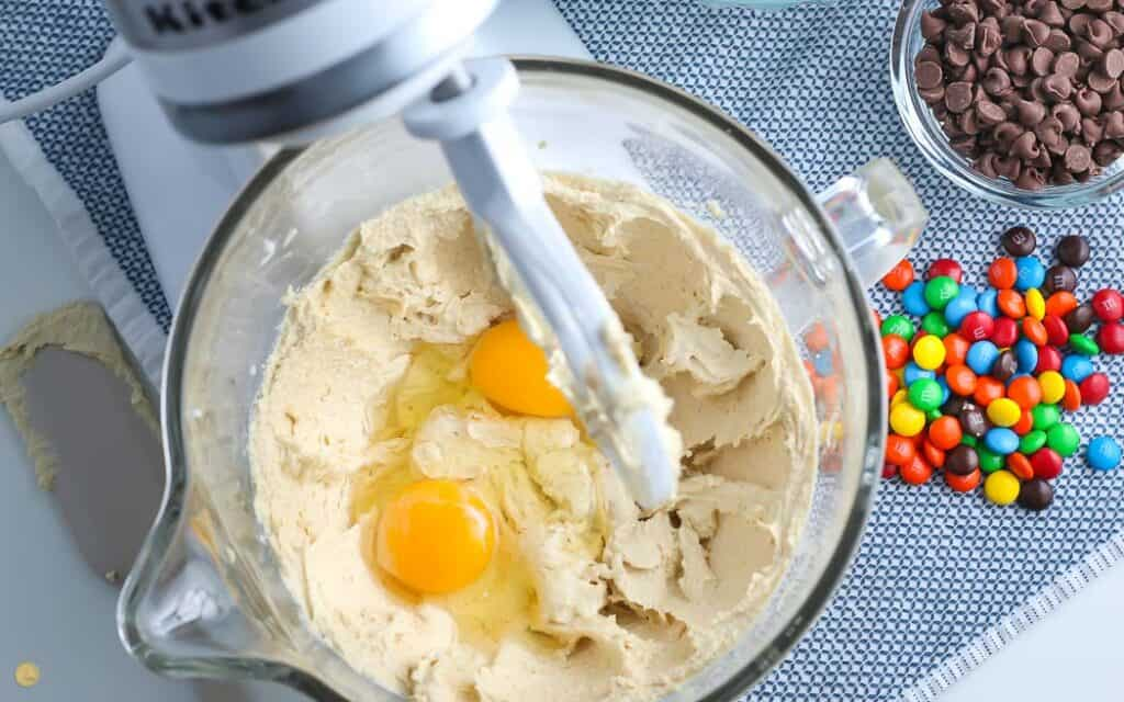 over head picture of stand mixer with cookie dough and eggs in the bowl on a blue placemat with a bowl of M&Ms next to it
