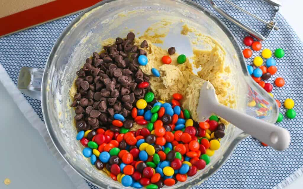 mixing bowl with cookie dough, M&M candies, and chocolate chips with a spatula on a blue placemat