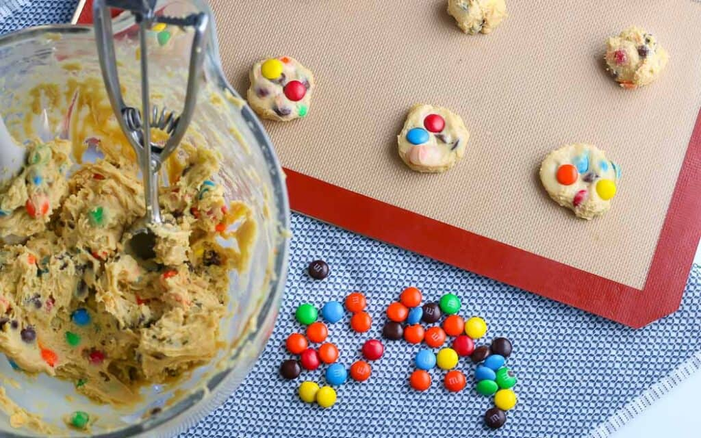 baking sheet with balls of cookie dough on it next to a mixing bowl with dough in it