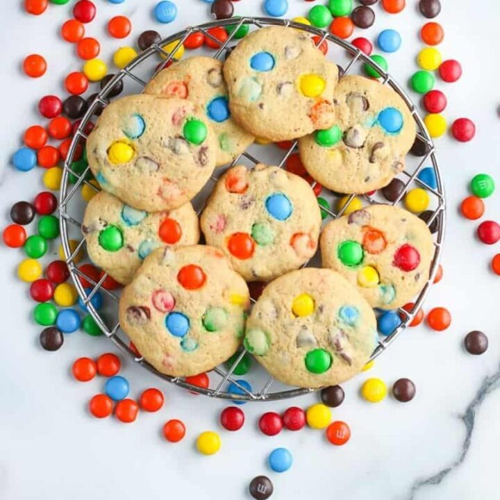 overhead square pic of m&M cookies on a metal rack