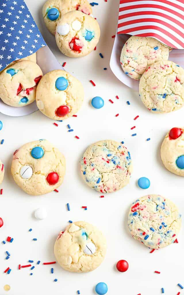 overhead shot of patriotic cookies in red white and blue bags surrounded by festive sprinkles