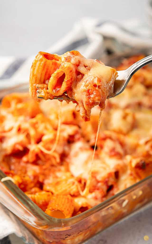 fork with pasta and melted cheese with casserole dish of baked pasta in the background