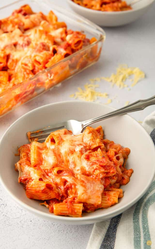 baked rigatoni in a white bowl with a fork