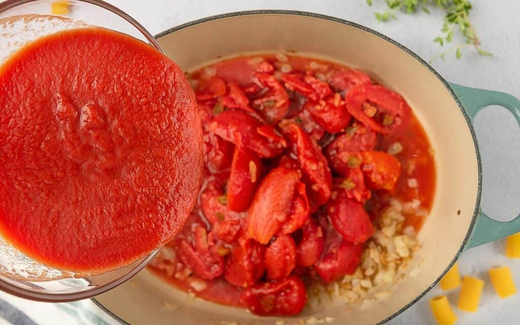 overhead picture of dutch oven with oil, onions, and tomatoes