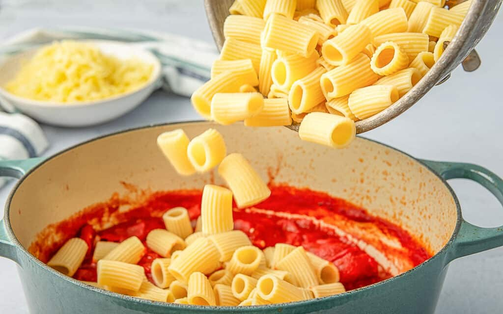 cooked pasta pouring into a pot of sauce