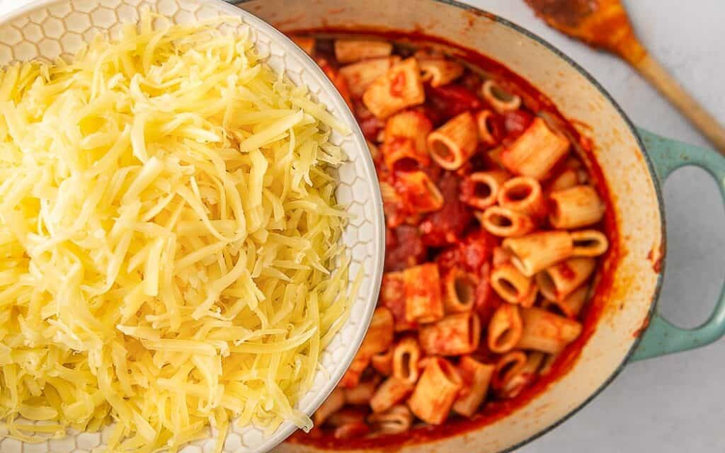 bowl of grated cheese over a pot of sauce