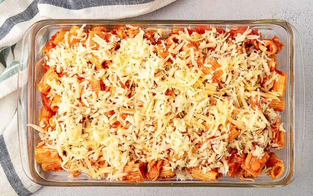 unbaked pasta with sauce in a clear dish covered in shredded cheese
