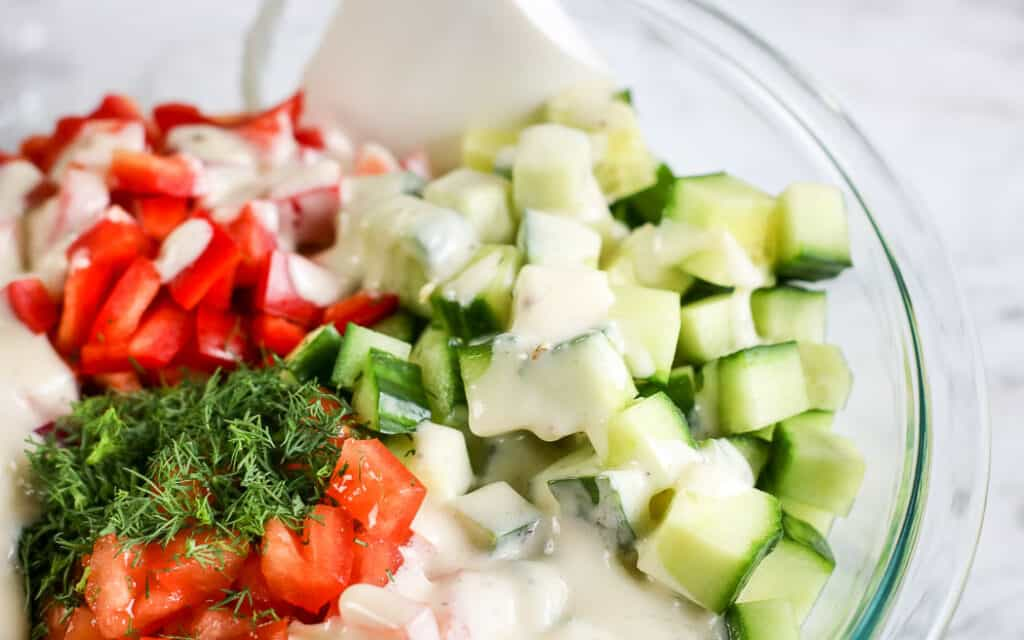 unmixed chopped tomatoes and cucumbers in a clear bowl with dressing poured on top with a white spatula