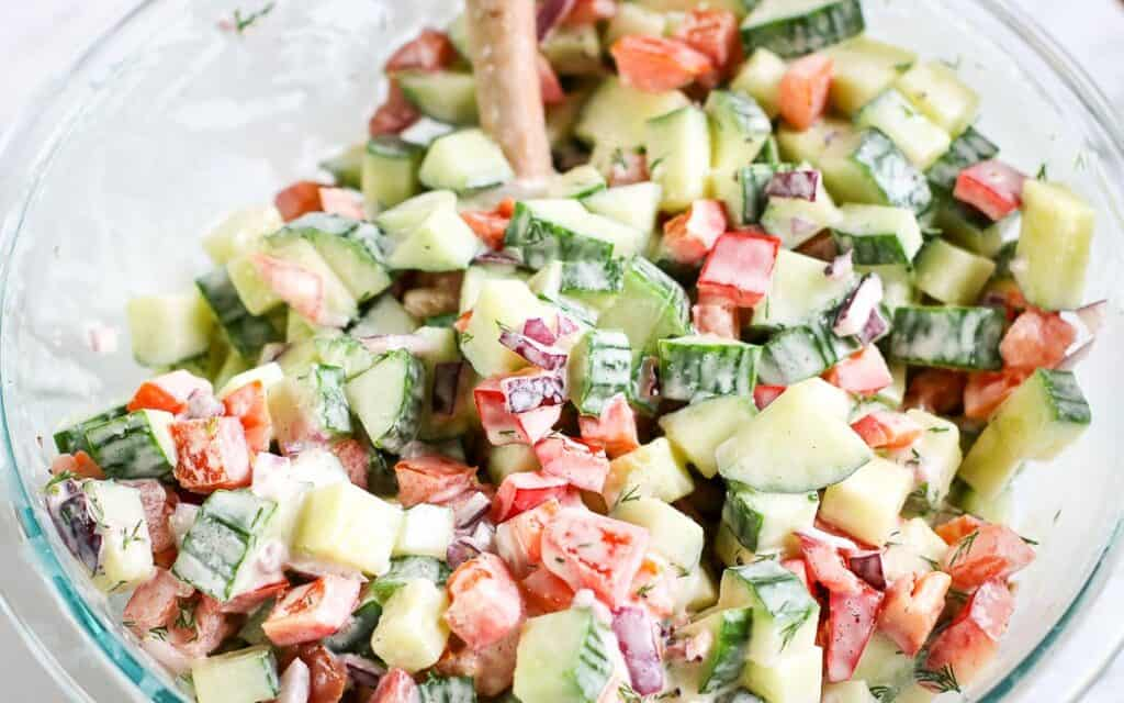 mixed chopped cucumber tomato salad in a clear bowl