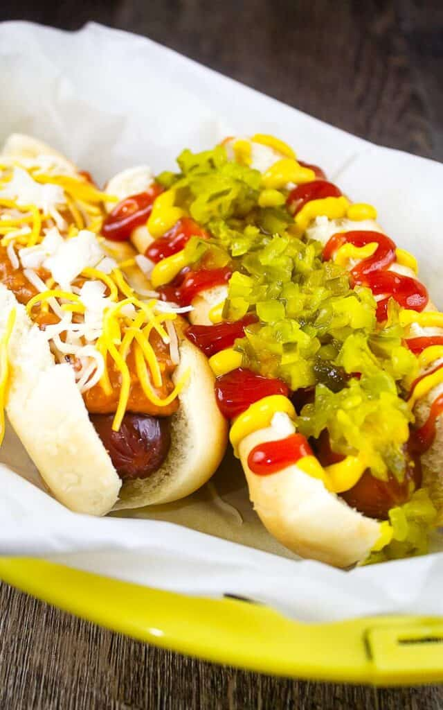 a chili cheese dog and a regular hot dog in a yellow basket lined with parchment paper