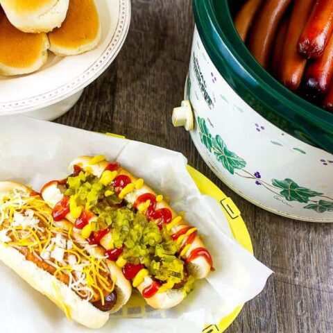 two dressed hot dogs in a paper basket next to a crockpot full of hot dogs