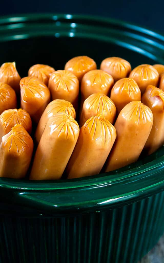 hot dogs standing on end in a green slow cooker bowl