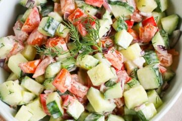 square picture of creamy cucumber tomato salad in a white bowl for recipe card