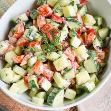 square picture of creamy cucumber tomato salad in a white bowl for recipe card