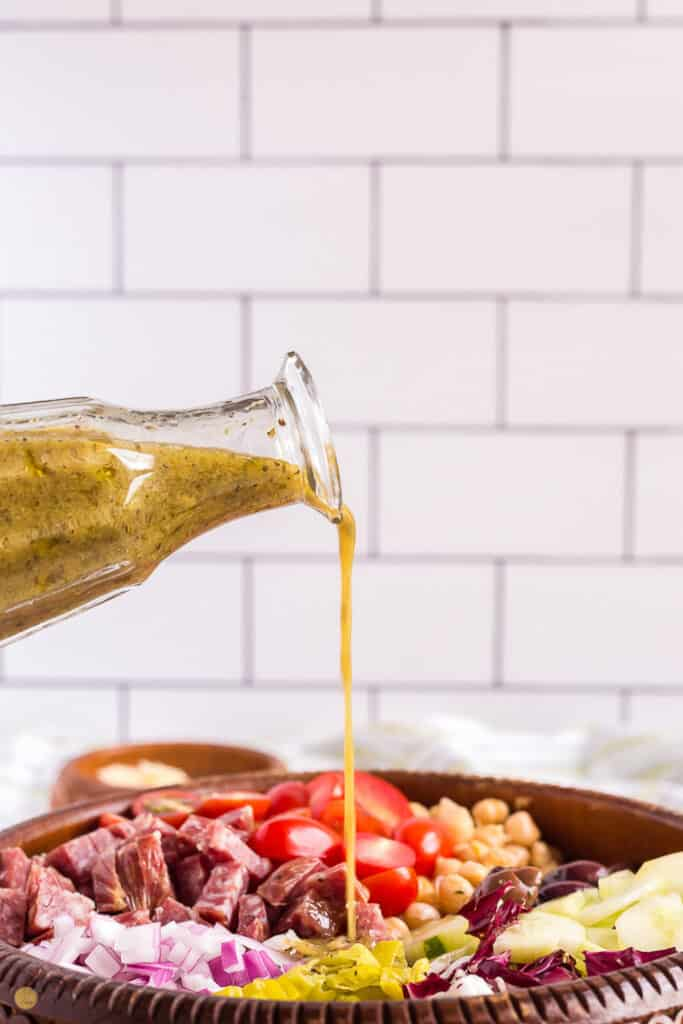 salad dressing being poured onto a salad in front of a white tile wall