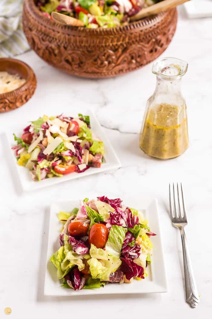 two side salads with forks on the plates and a bottle of salad dressing to the right