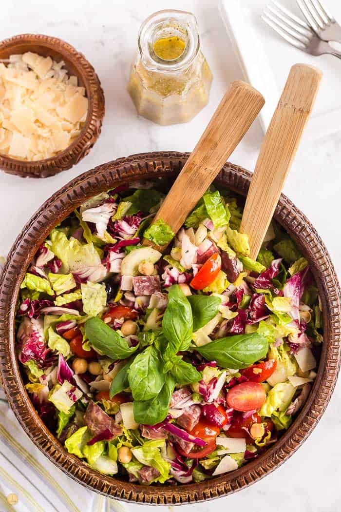 mixed Italian chopped salad in a wood bowl with wood serving spoons in it. Cheese and dressing off to the side