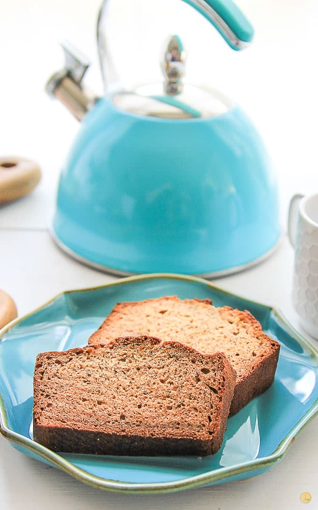two slices of banana bread on a teal plate with a tea kettle in the background