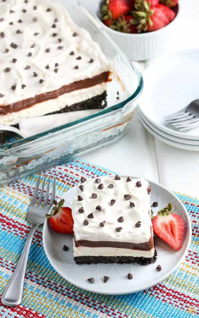 overhead picture of a slice of chocolate lasagna on blue plate next to full dish