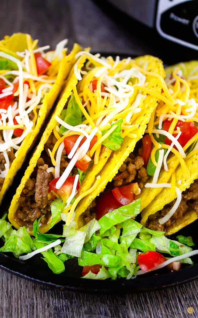 black plate with three tacos on it