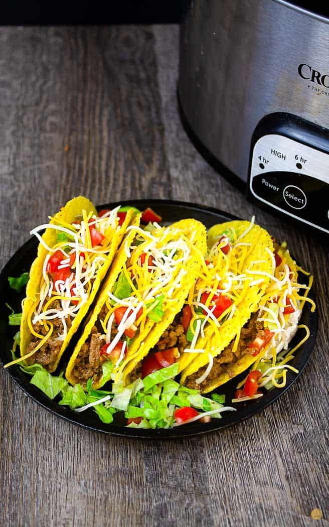 4 filled tacos on a black plate next to a crock pot