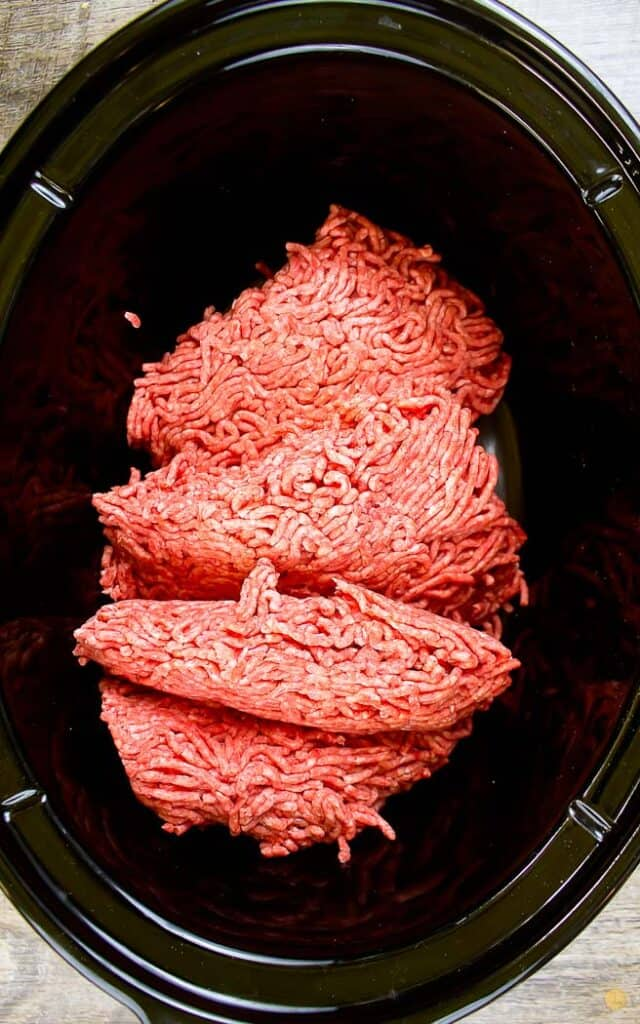 raw ground beef in a black crock pot bowl