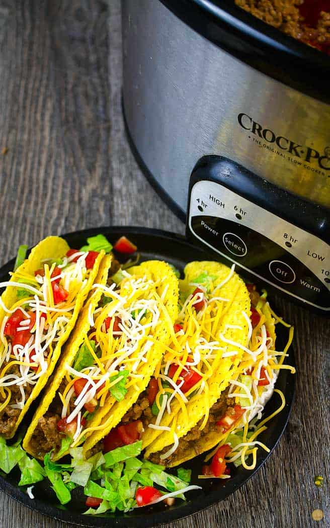 four dressed hard tacos on a black plate next to a crockpot