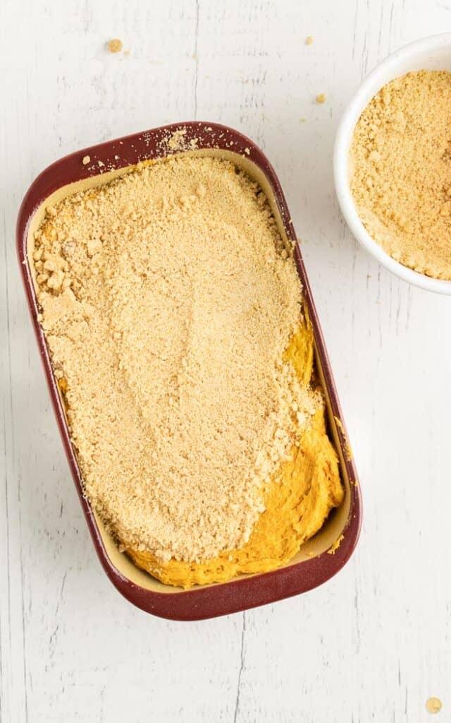 pumpkin bread batter in loaf pan covered in streusel top