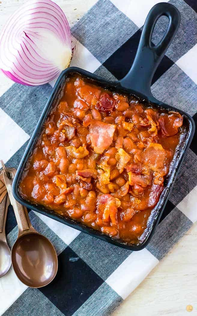 overhead picture of beans in a square pan on a checkerboard napkin with measuring spoons on the side