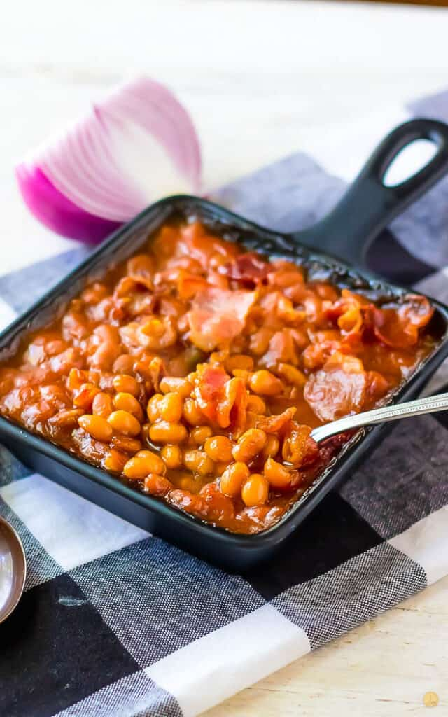 spoon scooping beans out of a square pan on a checkerboard napkin