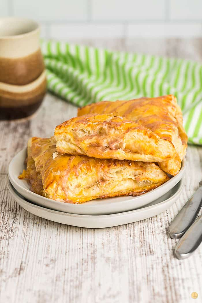 two apple turnovers on a stack of grey plates