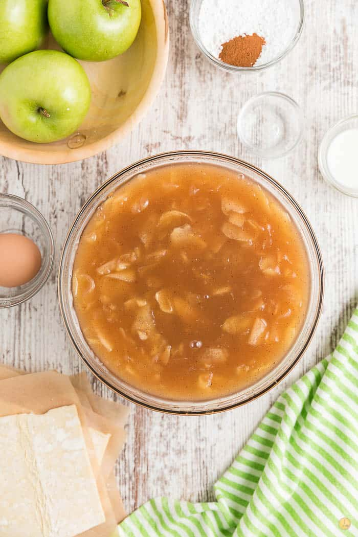 apple pie filling in a clear bowl on a white backdrop