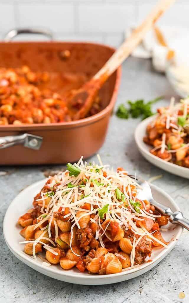 beefaroni on a white plate covered with shredded cheese