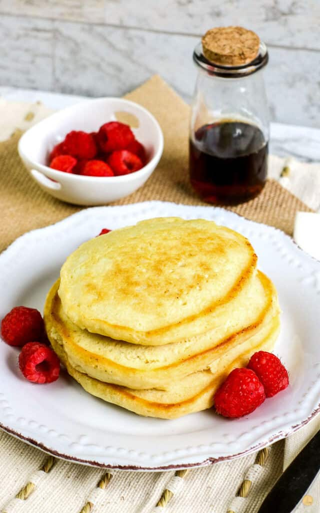 old fashioned pancakes on a white plate with raspberries