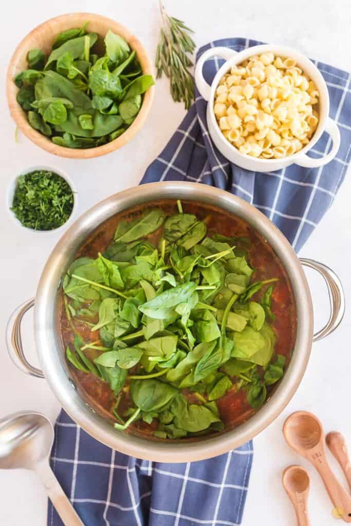 metal pot with soup and fresh spinach on a blue napkin