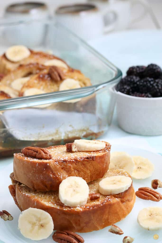 two slices of french toast with bananas and pecans